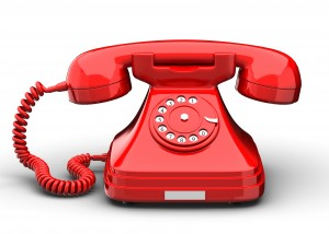 An old fashioned antique rotary style telephone isolated over a white background.